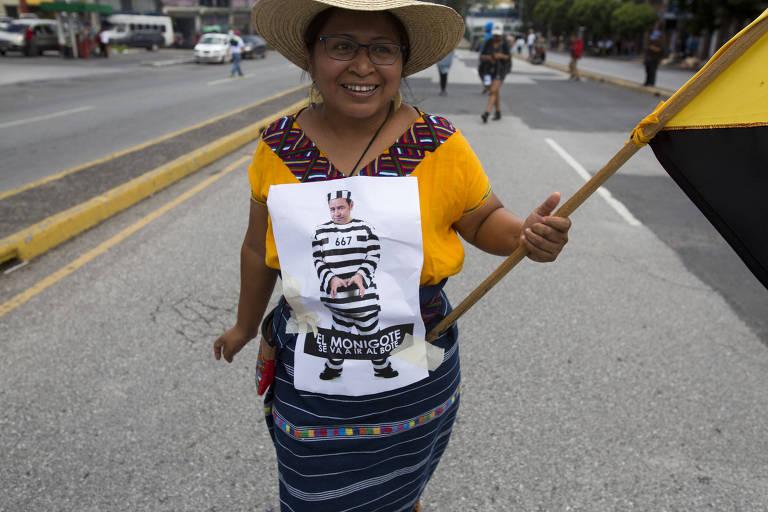Mulher participa de protesto com cartaz com caricatura do presidente Jimmy Morales na Cidade da Guatemala