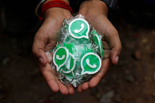 A WhatsApp-Reliance Jio representative displays key chains with the logo of WhatsApp for distribution during a drive by the two companies to educate users, on the outskirts of Kolkata