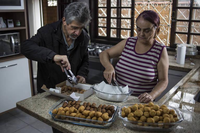 Glória e João em pé separam doces de festa preparados na cozinha de casa