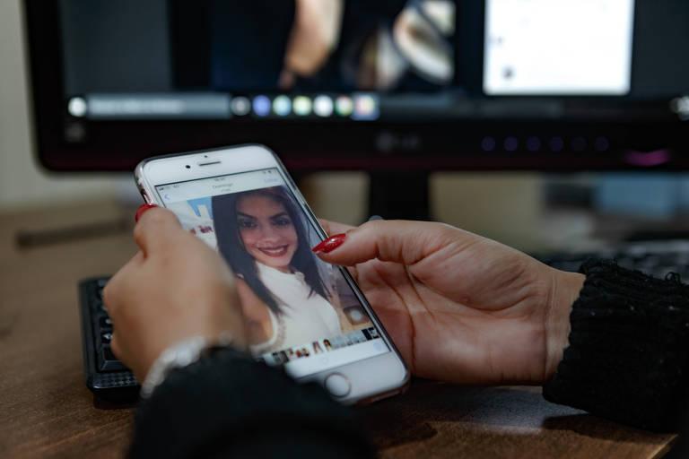 Mãos de mulher, com unhas pintadas de vermelho, seguram um celular branco em frente a um monitor de computador, do qual aparece apenas a base. No celular, aparece a foto de uma jovem mulher branca, de cabelos castanhos longos e um sorriso
