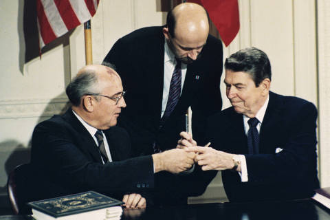 FILE - In this Dec. 8, 1987 file photo U.S. President Ronald Reagan, right, and Soviet leader Mikhail Gorbachev exchange pens during the Intermediate Range Nuclear Forces Treaty signing ceremony in the White House East Room in Washington, D.C. Gorbachev's translator Pavel Palazhchenko stands in the middle. Trump's announcement that the United States would leave the Intermediate-Range Nuclear Forces, or INF, treaty brought sharp criticism on Sunday Oct. 21, 2018, from Russian officials and from former Soviet President Mikhail Gorbachev, who signed the treaty in 1987 with President Ronald Reagan. (AP Photo/Bob Daugherty, File) ORG XMIT: XAZ102