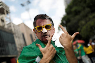 Supporter of Jair Bolsonaro, far-right lawmaker and presidential candidate of the Social Liberal Party (PSL), wears a mask with the image of Bolsonaro as he gestures during a demonstration in Sao Paulo