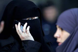 FILE PHOTO: A women , wearing a niqab despite a nationwide ban on the Islamic face veil, gives a phone call outside the courts in Meaux