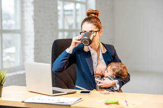 Multitasking businesswoman with her son working at the office