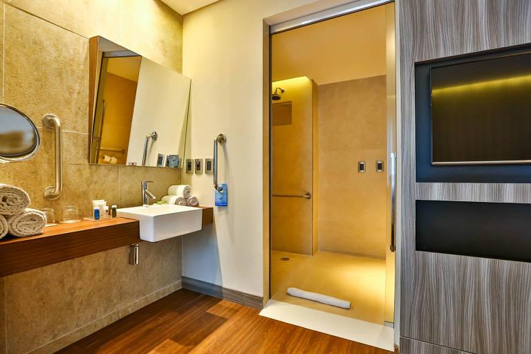 Banheiro de hotel com barras de apoio e rampa