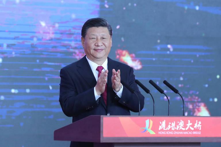 Xi Jinping aparece de terno preto, camisa branca e gravata vermelha diante de um púlpito vinho com microfones; ao fundo, um telão exibe imagens aéreas da região de Hong Kong