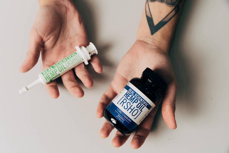 Duas mãos em fundo branco: uma segura uma seringa e outra, um frasco de remédios
