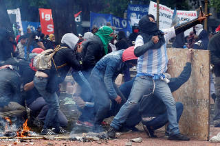 A protester uses a slingshot to hurl stones at the police during clashes outside the Congress in Buenos Aires