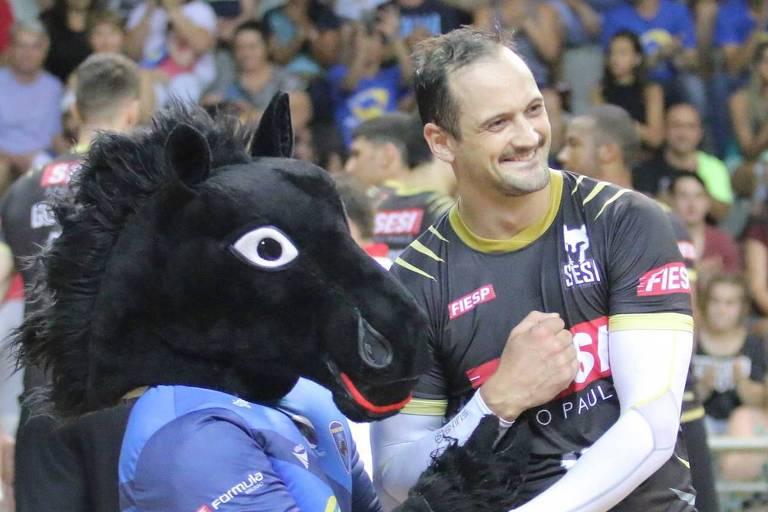 Lipe, ponteiro do Sesi, cumprimenta a mascote do Vôlei Ribeirão em jogo de 2017