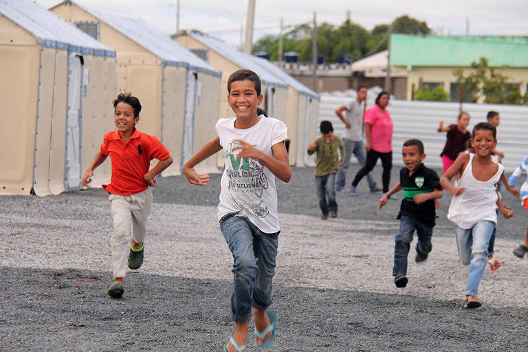 Grupo de cinco crianças corre em uma rua formada por cabanas de lona de cor bege