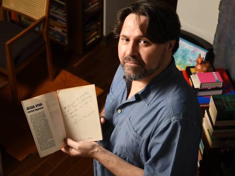 """O escritor Marcelino Freire segura a primeira edição do livro """"Água Viva"""", de Clarice Lispector"""
