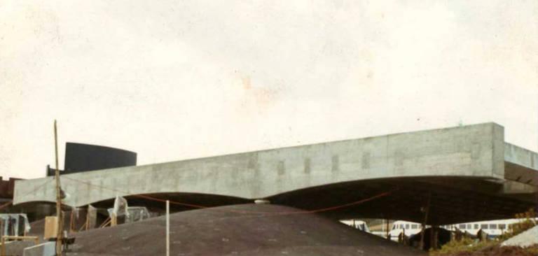Foto mostra o pavilhão de Osaka em construção; é possível ver a cobertura apoiando-se no terreno