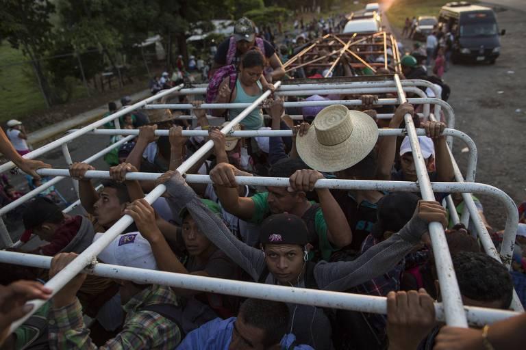 Grupo de 20 homens se segura na caçamba de um caminhão para animais. Um deles carrega um chapéu redondo grande. Ao fundo, outros carros levam mais pessoas.