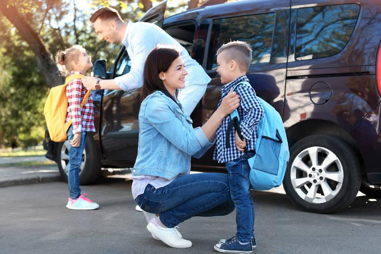 Pais se despedem de seus filhos na porta da escola