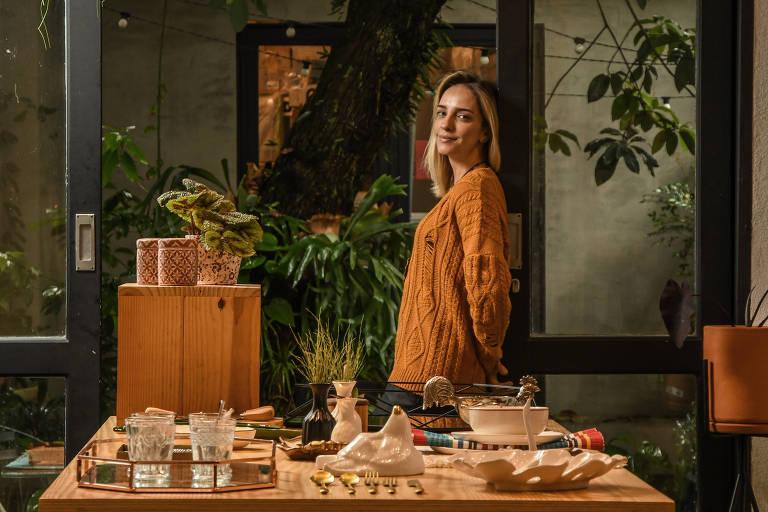 Mulher apoiada em mesa de madeira, há objetos de decoração sobre a mesa