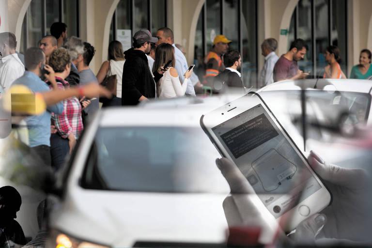 Montagem em foto de passageiros que aguardam carros de aplicativos no desembarque do aeroporto de Congonhas, na zona sul de São Paulo