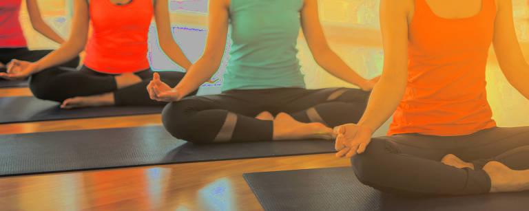 Mulheres exercitando e sentado em posição de lótus em aula de yoga