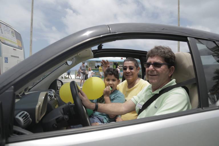 Com o neto no colo, cantor Zeca Pagodinho passa em frente ao condomínio de Bolsonaro