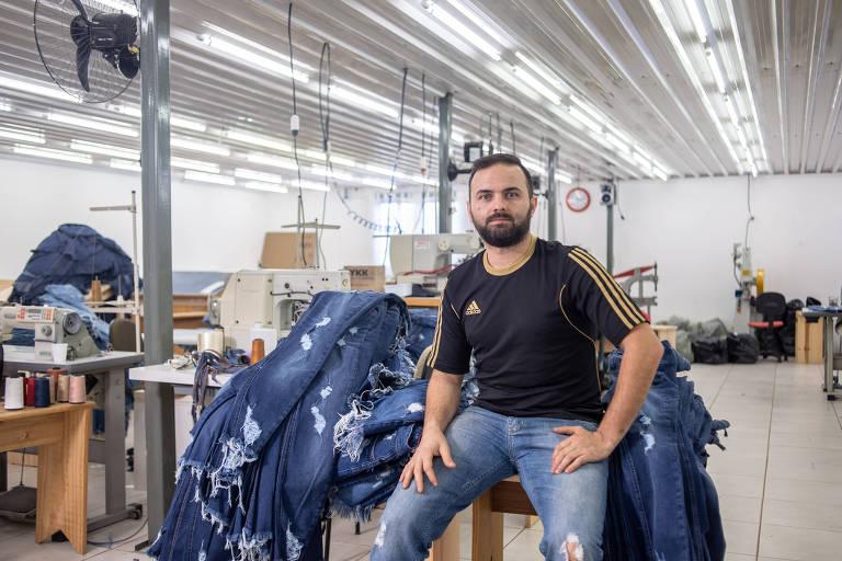 Homem de camisa presta e calça jeans ao lado de máquina de costura