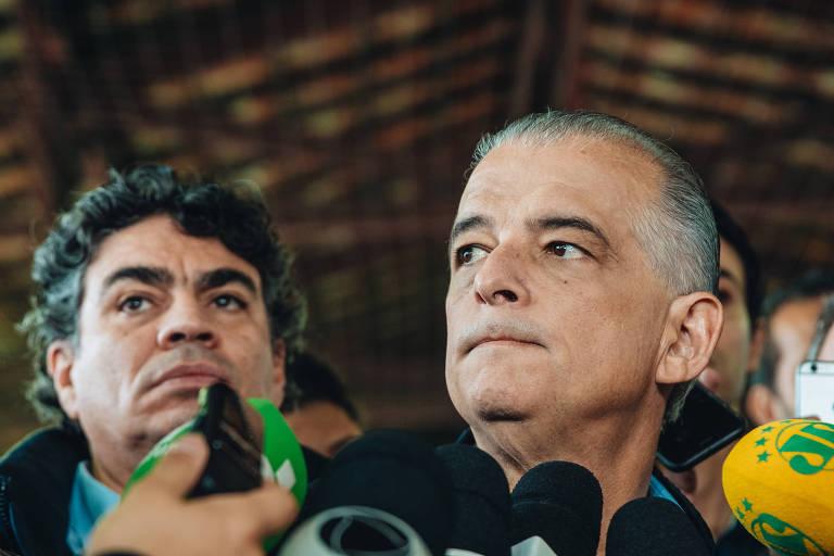 Cercado por microfones, o governador Márcio França no colégio em que votou no domingo (28), na capital paulista; à esquerda, seu braço-direito, Claudio Valverde