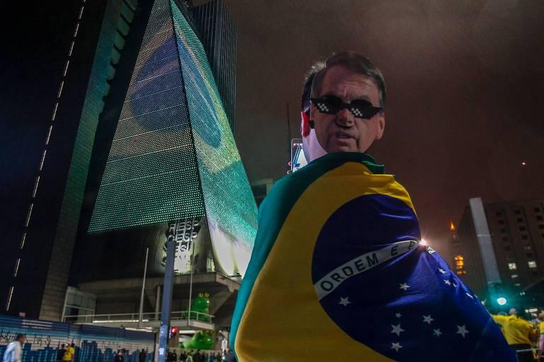 Homem está de costas, com uma máscara de Bolsonaro na cabeça e enrolado na bandeira do Brasil. Ao fundo, o prédio da Fiesp.