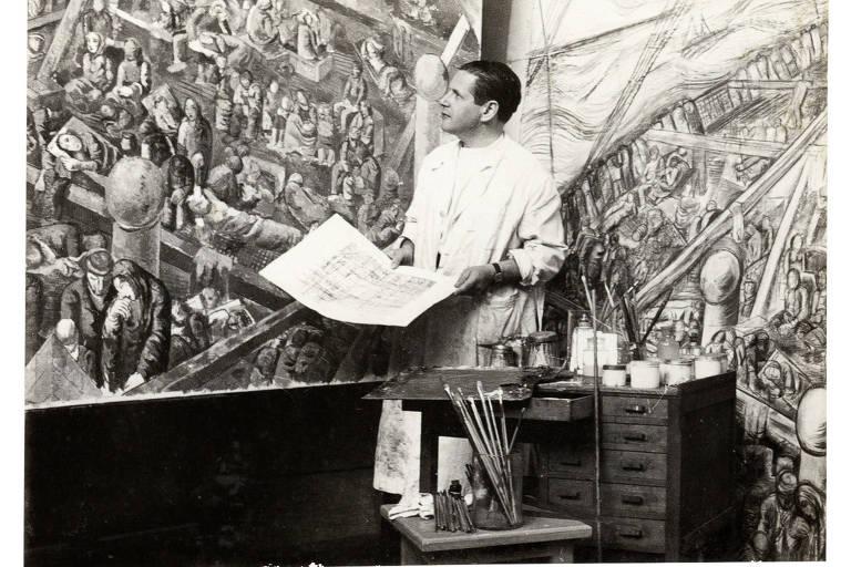 Segurando com as duas mãos uma folha de rascunho, o artista Lasar Segall observa uma de suas obras, em seu ateliê