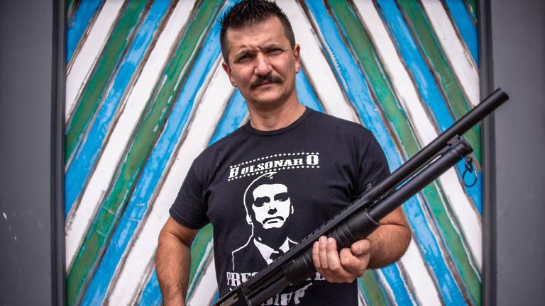 Homem de rifle na mão e camiseta preta com o rosto e nome de Bolsonaro
