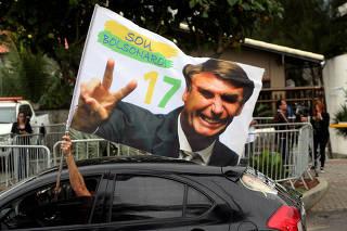 A supporter of Brazil's new president-elect, Jair Bolsonaro, celebrates in front of Bolsonaro's condominium at Barra da Tijuca neighborhood in Rio de Janeiro