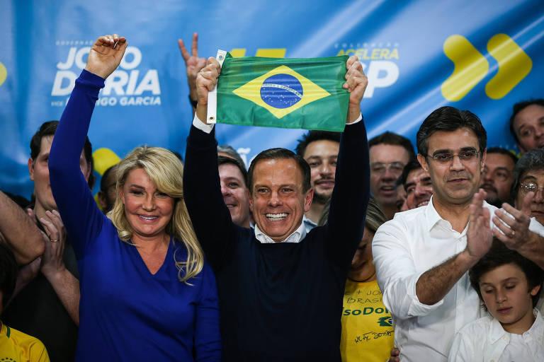 Doria levanta bandeira na festa da vitória, entre a mulher, Bia, e o vice, Rodrigo Garcia