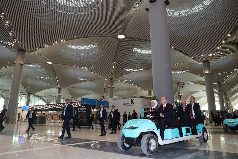Ao lado da mulher Emine Erdogan, o presidente turco, Tayyip Erdogan, dirige carrinho de transporte interno do novo aeroporto de Istambul, inaugurado nesta segunda (29), Dia da República na Turquia