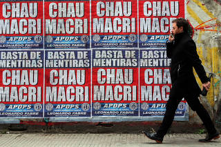 A man walks past billboards in Buenos Aires' financial district