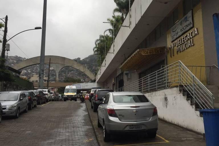 À direita, o prédio da delegacia, com carros parados em frente a ela. Ao fundo o arco e o morro da favela da Rocinha
