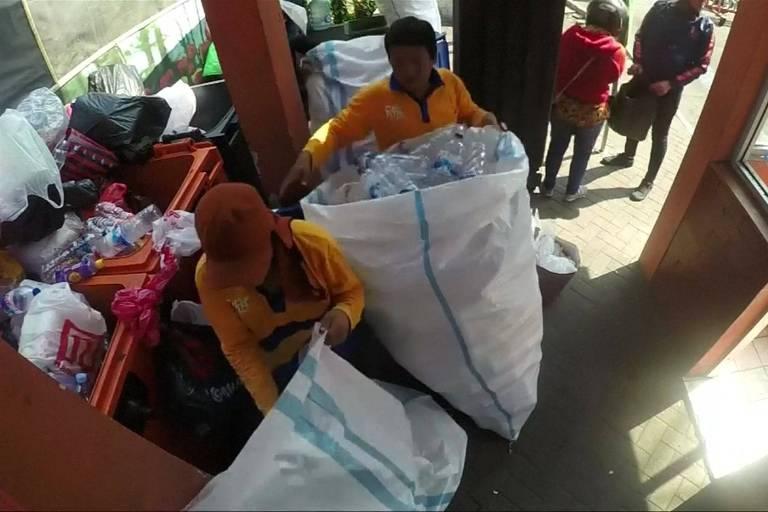 Funcionários recolhem embalagens plásticas usadas para comprar bilhetes de ônibus em Surabaya, na Indonésia