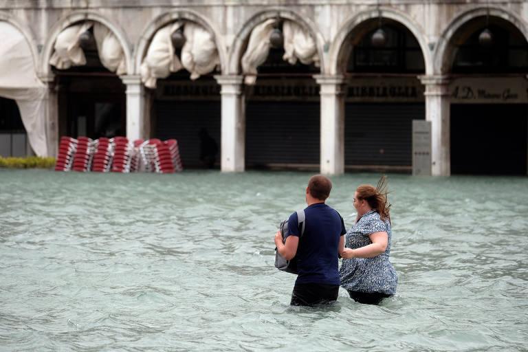 Um casal anda no alagamento na praça São Marco