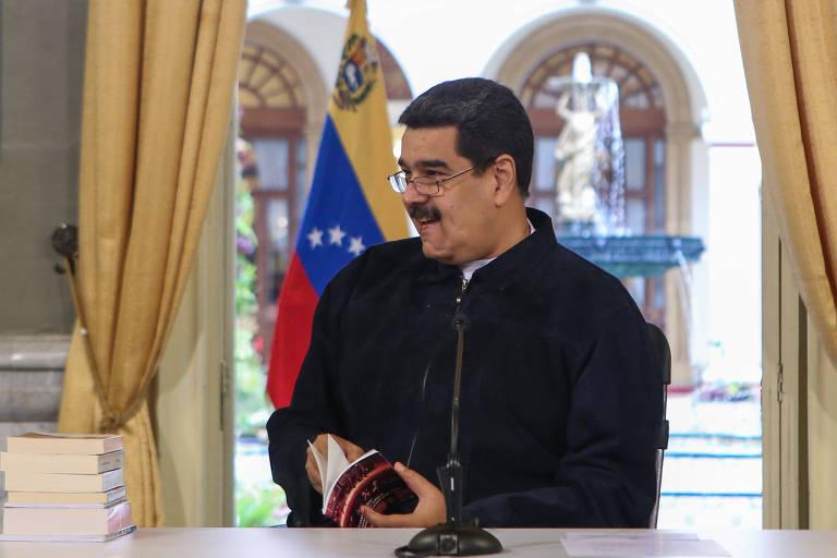 Vestindo uma camisa preta e sentado à uma mesa, Maduro olha para o lado esquerdo enquanto folheia um livro. Ao fundo, uma janela com uma bandeira da Venezuela.