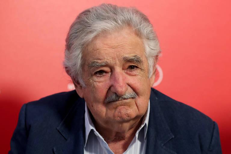 Mujica aparece sério à frente de um painel laranja.