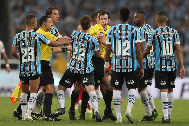 Jogadores do Grêmio cercam o árbitro após marcação de pênalti para o River Plate