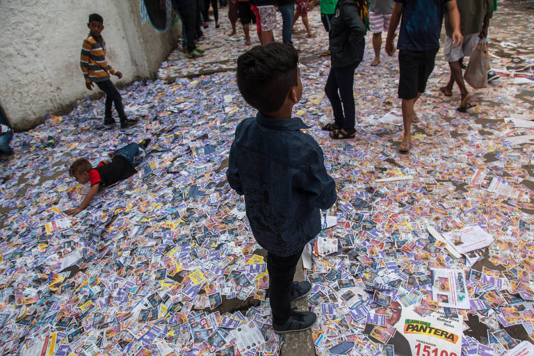 Santinhos espalhados pelo chão em frente a escola em Belford Roxo, quarto maior colégio eleitoral do estado do Rio. Cidade vive realidade violenta e aderiu a Bolsonaro neste ano