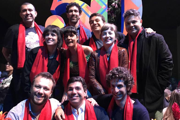 """Chefs brasileiros posam em frente o símbolo do prêmio """"50 Best"""", com lenços vermelhos"""
