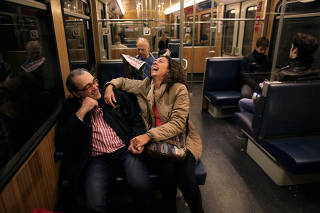 FILE PHOTO: Abel and his wife Oliva laugh as they sit on a train after she arrived from Spain to spend a week in Munich