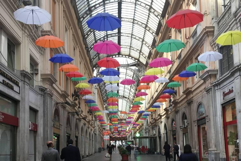 A galeria Giuseppe Mazzini, com lojas de grife, e guarda-chuvas coloridos abertos pendurados no teto