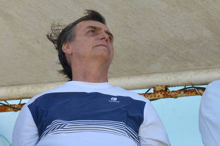 Brazil's new president-elect, Jair Bolsonaro, watches airplanes performing near his condominium at Barra da Tijuca neighbourhood in Rio de Janeiro