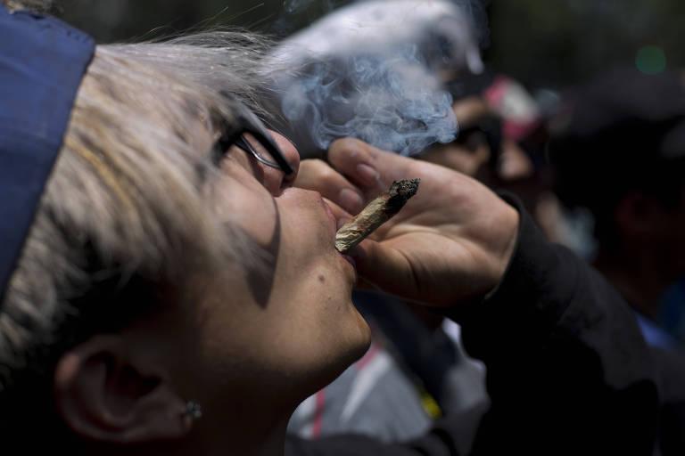 Homem segura cigarro de maconha com a mão e fuma, enquanto olha para o alto