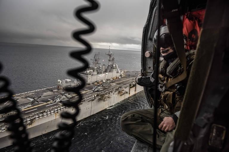 Foto é feita de dentro do helicóptero, e o fuzileiro aparece à direita. Do lado de fora da porta vê-se o navio.