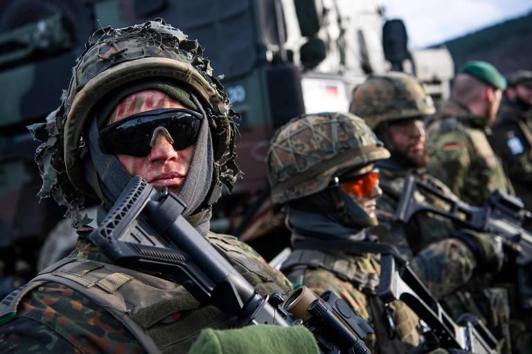 Quatro soldados alemães com capacetes, óculos de sol e armados com metralhadoras fazem fila ao lado de blindado