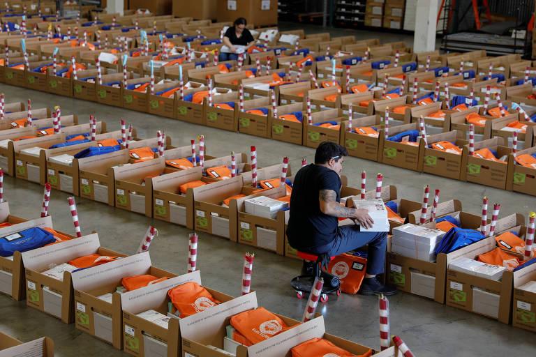 Kits eleitorais em caixas formam cinco filas. Na segunda, um homem com camisa preta inspeciona um deles com um livro e, na quarta, uma mulher faz o mesmo.