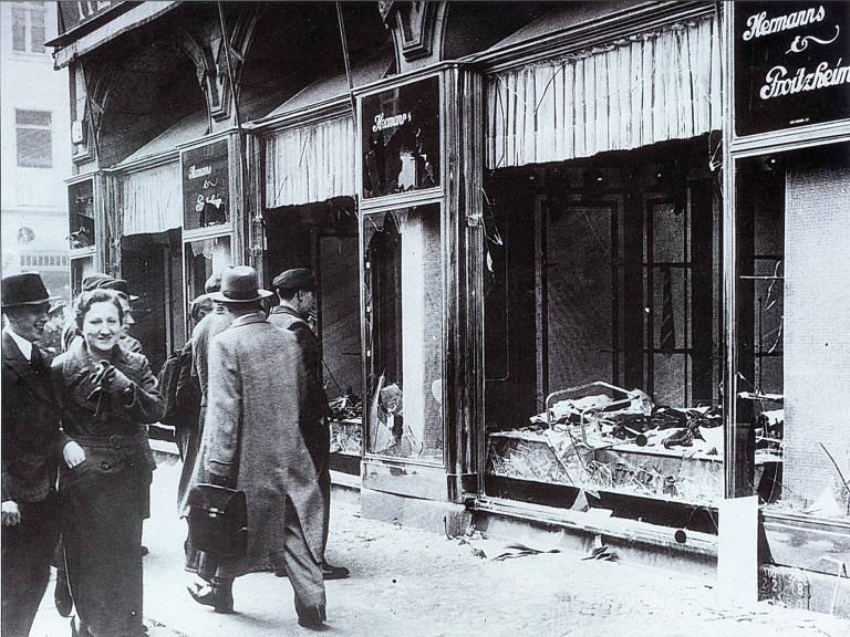 Pedestres passam por vitrine destruída após ataques da Kristallnacht, em novembro de 1938