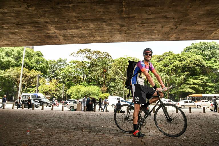 Homem em cima de bicicleta com árvores ao fundo