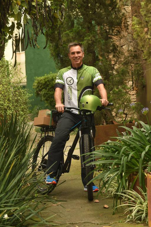 Homem em cima de bicicleta num jardim