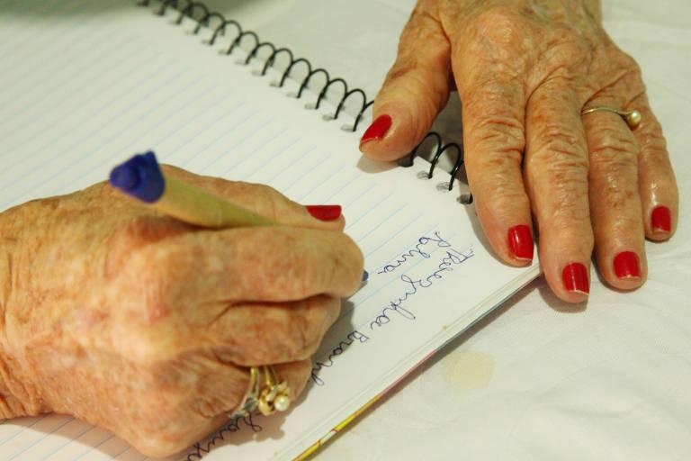 Idosa escreve em caderno